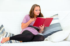 Surprised reading  book on sofa at home Stock Images