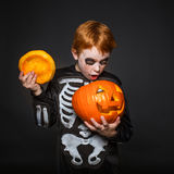 Surprised red haired boy in skeleton costume holding a orange pumpkin. Halloween. Royalty Free Stock Image