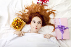 Surprised red-haired girl in bed with gifts. Royalty Free Stock Image