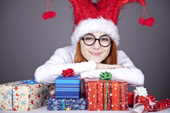 Surprised red-haired girl in christmas cap Stock Photos