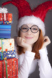Surprised red-haired girl in christmas cap Stock Photo