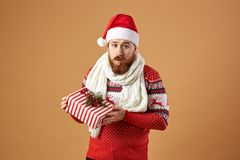 Surprised red-haired man with beard dressed in a red and white sweater with deer, white knitted scarf and a hat of Santa royalty free stock image