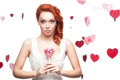 Surprised red-haired woman holding lollipop Royalty Free Stock Image
