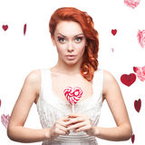 Surprised red-haired woman holding lollipop Stock Photography