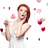 Surprised red-haired woman holding lollipop Stock Images