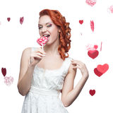 Surprised red-haired woman holding lollipop Stock Image