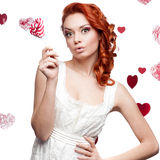 Surprised red-haired woman holding lollipop Stock Photo