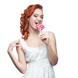 Surprised red-haired woman holding lollipop Royalty Free Stock Photos