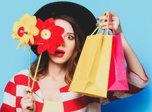 Woman with pinwheel and shopping bags stock photos