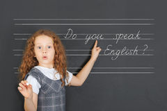 Surprised redhead girl asks a question -  Do you speak English. Stand near blackboard in the classroom. Education concept Royalty Free Stock Image