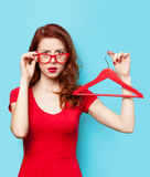 Surprised redhead girl with hanger Royalty Free Stock Image