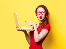 Surprised redhead girl with laptop. On yellow background Stock Images
