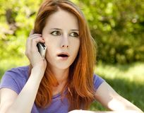 Surprised redhead girl with mobile phone Stock Image