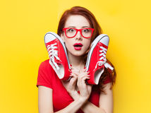 Surprised redhead girl in red dress with gumshoes Royalty Free Stock Images