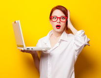 Surprised redhead girl in white shirt with computer Royalty Free Stock Photos