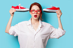 Surprised redhead girl in white shirt with gumshoes Royalty Free Stock Photo