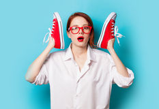 Surprised redhead girl in white shirt with gumshoes Stock Photo