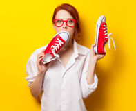 Surprised redhead girl in white shirt with gumshoes Royalty Free Stock Image