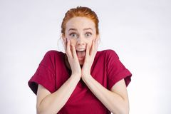 Surprised redhead woman wide open mouth and touching her head. white background. Surprised redhead young woman in red shirt wide open mouth and touching her head Royalty Free Stock Photos