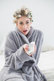 Surprised relaxed blonde woman in hair curlers using a remote control Stock Photography