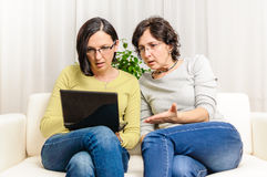 Surprised sad women browsing home laptop Stock Photography