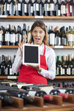 Surprised Saleswoman Showing Blank Digital Tablet In Wine Shop Stock Photography