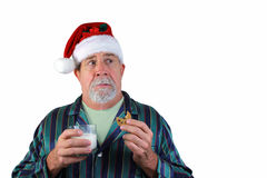 Surprised Santa. A surprised Santa caught in the act of eating a chocolate chip cookie and drinking milk left by the kids on Christmas Eve Stock Images