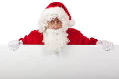 Surprised Santa Claus holding Christmas ad board Stock Images