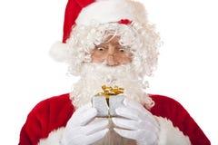Surprised Santa Claus holding Christmas gift Stock Photo