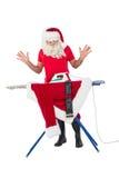 Surprised santa claus ironing his jacket Royalty Free Stock Images