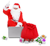 Surprised Santa claus with laptop and presents Stock Image
