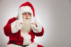 Surprised santa claus looks to side. Surprised santa claus looks to e with palms on his face on grey background Stock Photography