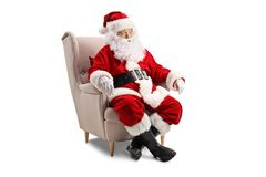Surprised Santa Claus sitting in an armchair royalty free stock photo