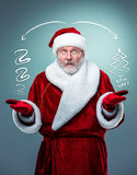 Surprised Santa Claus. Wondering Santa Claus looking at the camera  in glasses with a gray beard and raised arms on a blue background Stock Photos