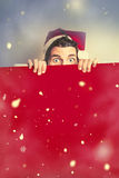 Surprised santa elf holding red christmas board. In a creative winter scene of falling snow. Merry xmas advert Royalty Free Stock Photo