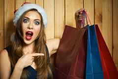 Surprised Santa girl hold shopping bag. Christmass gifts concept. Finger pointing on paper bag Royalty Free Stock Image