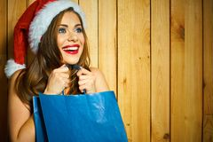 Surprised Santa girl hold shopping bag. Christmass gifts concept. Happy young woman Stock Image