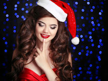 Surprised Santa. happy smiling girl with finger on lips. Beautiful woman model in red hat over christmas party lights background. Stock Photos