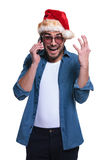 Surprised santa man is screaming on the phone. Shocked man in santa claus hat is talking on the phone and screams of joy Stock Images