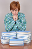 Surprised and scared woman and books. Surprised and scared  woman sitting on the brown table with books wondering how much she has to read Stock Photography