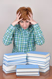 Surprised and scared woman and books. Surprised and scared  woman sitting on the brown table with books wondering how much she has to read Stock Image
