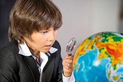 Surprised school boy with globe and lens Royalty Free Stock Photos