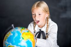 Surprised school girl with globe Stock Photography