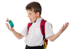 Surprised schoolboy with alarm clock in hand Stock Photography