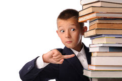 Surprised schoolboy with huge stack of books Royalty Free Stock Photography