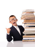 Surprised schoolboy with huge stack of books Stock Image