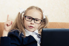Surprised schoolgirl in glasses with laptop Stock Photo