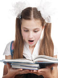 Surprised schoolgirl reading textbook. Stock Photo