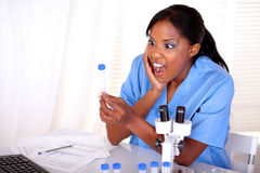 Surprised scientific woman looking to test tube Stock Photo