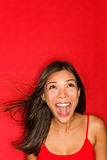 Surprised screaming woman looking up. At copy space on red background. Beautiful young shocked mixed race Caucasian / Asian female model amazed Royalty Free Stock Image
